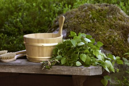 Traditional Finnish birch sauna whisk and wooden water pall Stock Photo