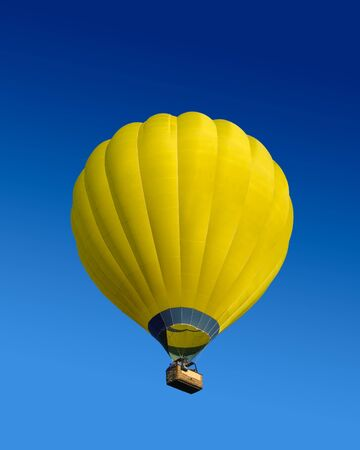 Yellow hot air balloon flying on dark blue sky background photo