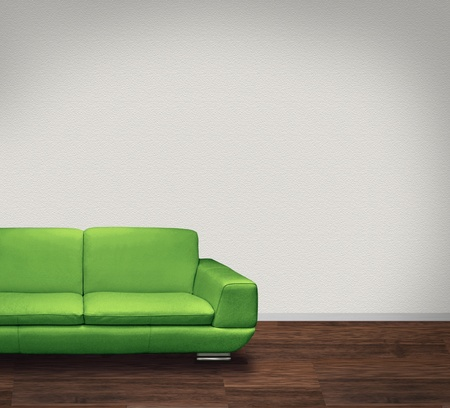 couch: Modern green leather sofa in room with dark floor and white walls