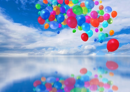 Colorful balloons on mirror cloudscape background photo