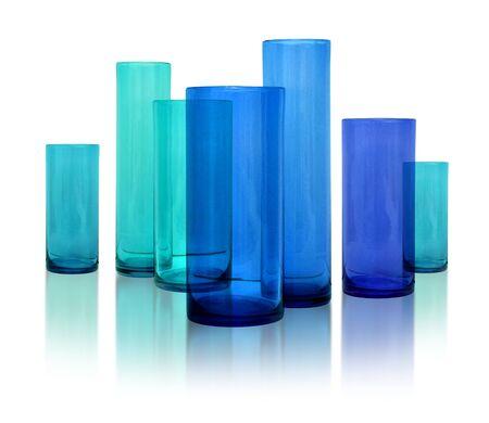 Fila de jarrones de siete moderna de vidrio azul sobre fondo blanco de reflexivo