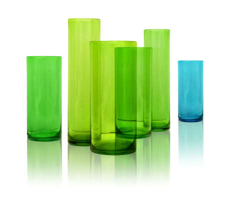 Modern colored glass vases row on white reflective background photo