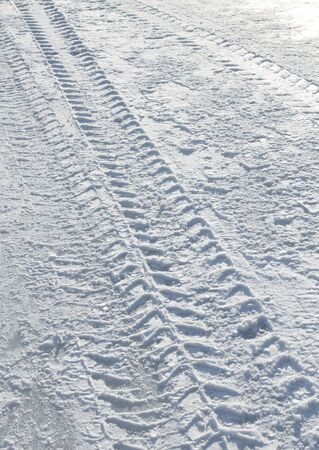 snow on the ground: Vehicle tyre tracks on snowy slippery road
