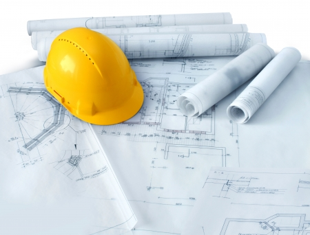 construction project: Construction plans drawings rolls and yellow hard hat helmet