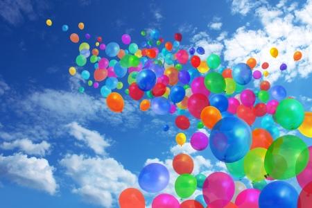 Gran cantidad de globos de colores volando sobre fondo de cielo azul Foto de archivo