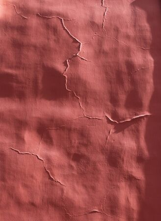 sidelight: Old cracked red plaster stone wall in sidelight