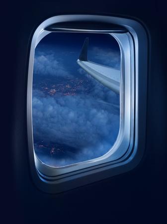 Night flight view from a jet plane window high above illuminated city Standard-Bild