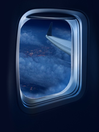 airplane window: Night flight view from a jet plane window high above illuminated city Stock Photo