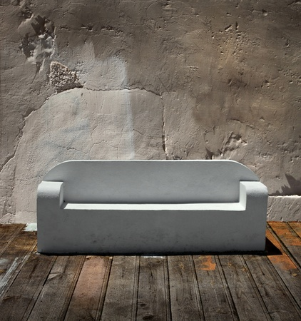 White marble  sofa on wooden floor and cracked stone wall background photo