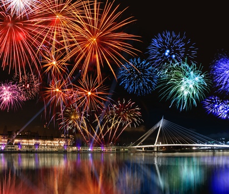 Colorful fireworks reflect from water,  beautiful bridge scenery