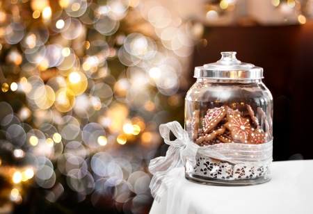 Gingerbread biscuits in glass jar, fantasy Christmas background