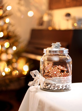 Homemade Christmas gingerbread biscuits in glass jar on table