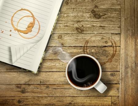 Taza de caf� negro y caliente en la mesa de madera �spera con los anillos de la mancha