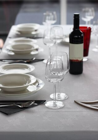 Casual table setting with cutlery, plates and wine glasses photo