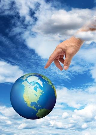mano de dios: Mano masculina alcanza a tocar el planeta Tierra, el fondo del cielo azul Foto de archivo