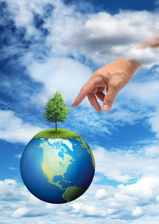 Male hand reaching to touch green tree on planet Earth photo