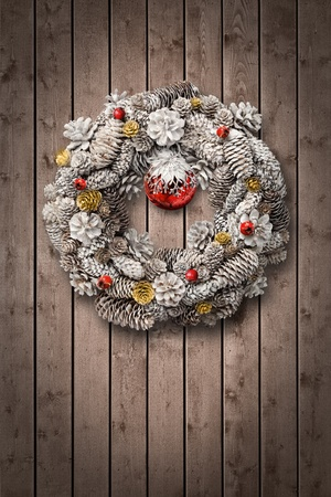 White Christmas wreath on brown wooden door background photo