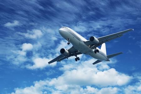 Avi�n de pasajeros aire volando sobre fondo azul cielo, blanco, nubes Foto de archivo