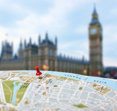 Red push pin pointing planned travel destination on London city map