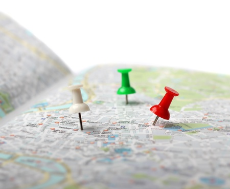 Push pins pointing planned travel destinations on city map Foto de archivo