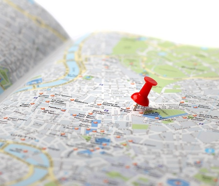 Red push pin pointing planned travel destination on city map Foto de archivo