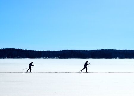 Skiers nordic skiing on frozen lake winter trail Stock Photo - 18834011