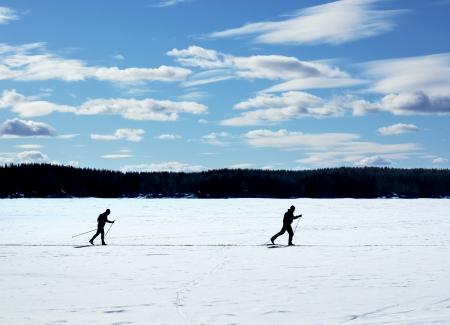 nordic ski: Skiers nordic skiing on frozen lake winter trail Stock Photo