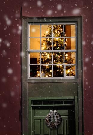 christmas cabin: Christmas tree seen outside of a window, snowfall background Stock Photo