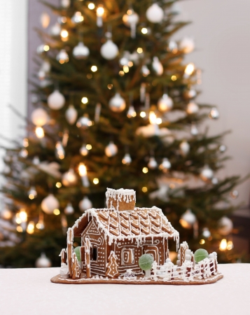 Gingerbread cottage house on real Christmas tree background photo