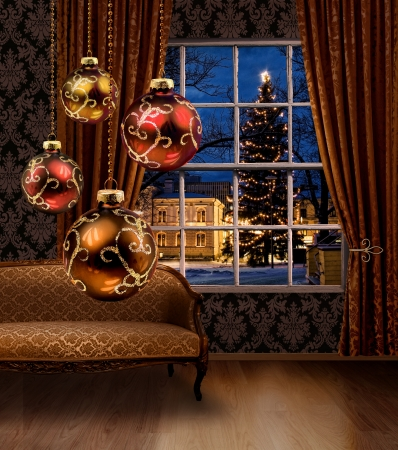Christmas balls hanging in front of town view window, classic furniture interior photo