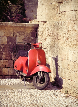 Red vintage scooter on old stone paved street photo