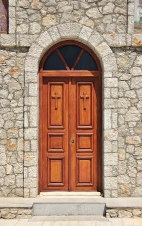 wood carving door: Stone church facade wooden double doors closed