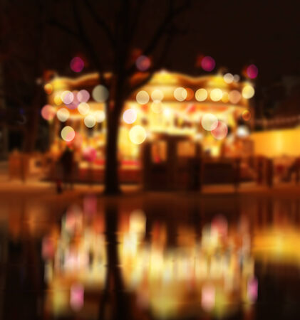 Carrousel by the water reflecting moving lights colorful bokeh photo