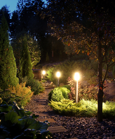 Illuminated home garden path patio lights in evening dusk Foto de archivo
