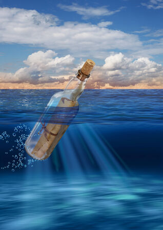 castaway: Message in bottle floating on open sea Stock Photo