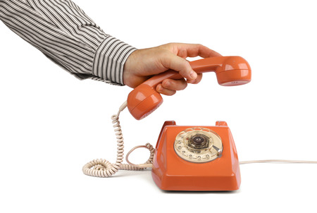 hang up: Male hand lifting vintage telephone handset, isolated on white Stock Photo