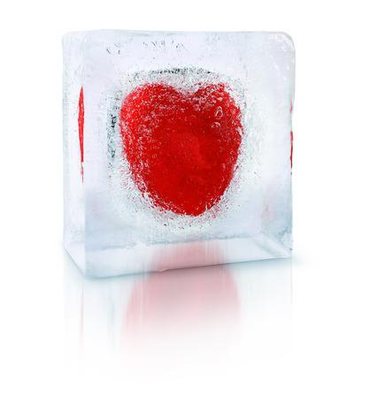 Red heart frozen inside an transparent ice cube block photo