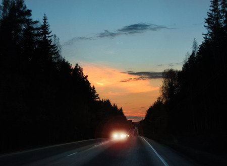 headlights: Approaching car headlights glare on evening road Stock Photo