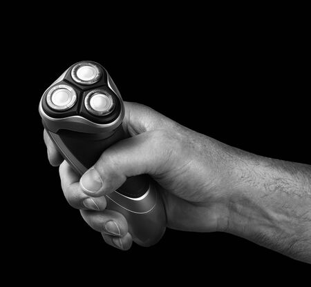 electric razor: Strong male hand holding electric razor shaver black background