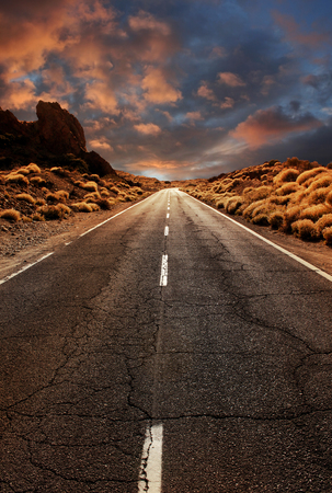 Grungy asphalt road leading through desert sunset landscape