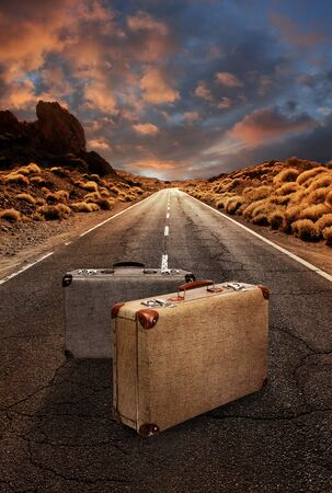 Two vintage suitcases in the middle of a grungy asphalt road leading through desert landscape Stock Photo
