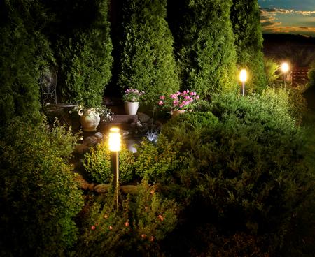 Illuminated home garden patio plants and fountain on evening dusk