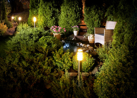 家の庭のテラスの植物および小さい噴水の近く夜ライトを点灯