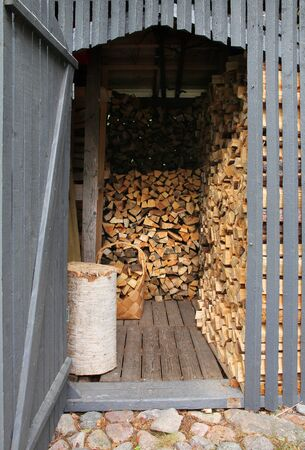storage: Wooden shed filled with piles of chopped firewood