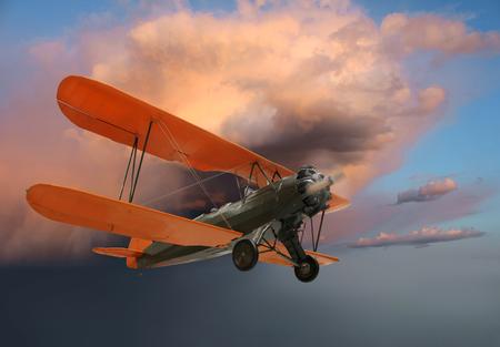 Old World War 1 biplane in flight on evening sky background
