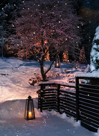 Lanterns in snowy winter garden yard snowfall