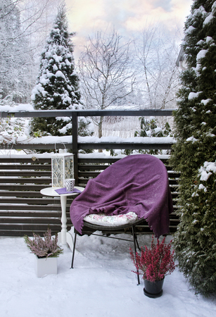 Winter feeling in snowy garden terrace- chair, blanket, table and heather decoration