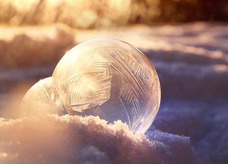 Magic of winter, frozen soap bubble ball on cold winter snow, crystal formations, sunlit background  版權商用圖片