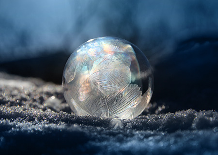 Frozen soap bubble ball on cold winter snow, crystal formations, dark background 版權商用圖片