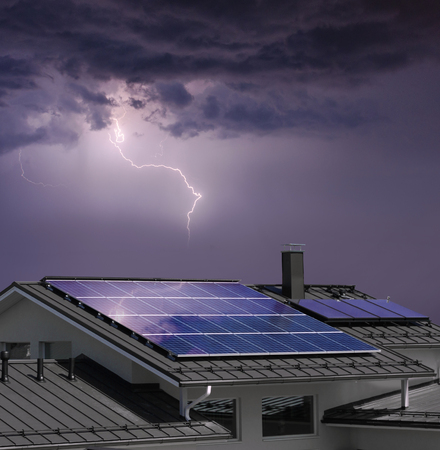 Solar panel system on house roof, dark sky, thunder and lightning background